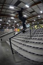 Tre Williams with a nollie front crook down the 10 stair rail.